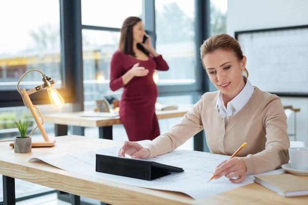 Proces pracy. zbliżenie na utalentowanego projektanta używającego tabletu z narzędziami i pracującego nad skomplikowanym szkicem, podczas gdy jej kolega rozmawia przez telefon komórkowy