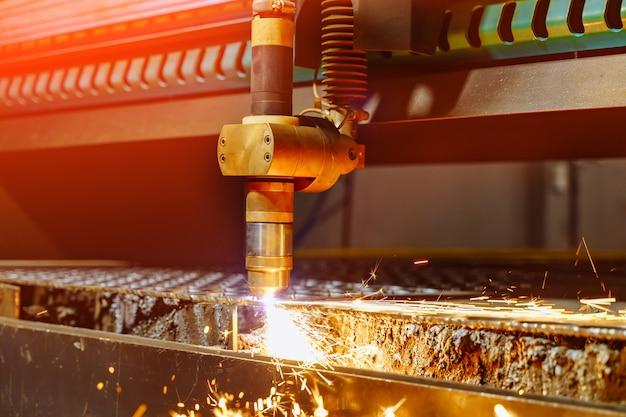 Proces przemysłowego cięcia maszynowego blachy i iskier wylatujących z lasera. technologia cięcia laserowego obróbki płaskich blach stalowych z iskrami.