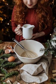 Proces przygotowania ciasta na drewnianym stole wśród przyborów kuchennych.