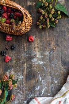 Proces przygotowania malinowego i jeżynowego ciasta, widok z góry na prosty drewniany stół