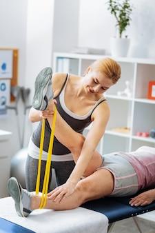 Proces rehabilitacji. miła profesjonalna terapeutka pracująca z pacjentem podczas terapii rehabilitacyjnej