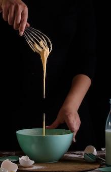 Proces robienia babeczek, powlekania kremu z torebki cukierniczej w rękach cukiernika.