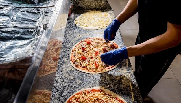 Proces robienia pizzy. ręki robi pizzy przy cukiernianą kuchnią szefa kuchni piekarz