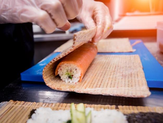 Proces robienia sushi i bułek w kuchni restauracji. ręce szefów kuchni z nożem.
