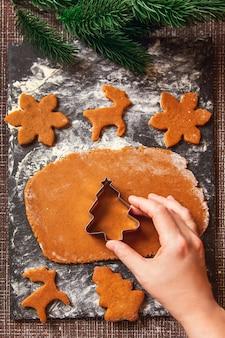 Proces robienia świątecznych ciasteczek imbirowych. kobieta trzyma pleśń w kształcie choinki na surowym cieście na imbirowe ciasteczka.