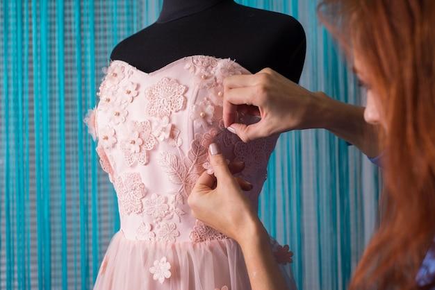 Proces robienia ubrań. profesjonalny projektant, ręcznie robiony rzemieślnik, szyje kwiaty na różowej sukience, na manekinie, w warsztacie. krawiectwo, sukienka damska. różowa suknia ślubna