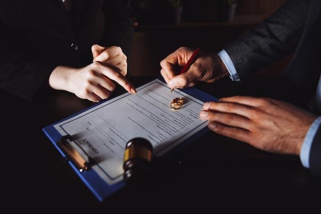Proces rozwodowy. mężczyzna i kobieta podpisują dokumenty z powodu zerwania.