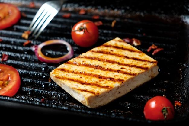 Proces smażenia kawałków tofu na specjalnej patelni grillowej