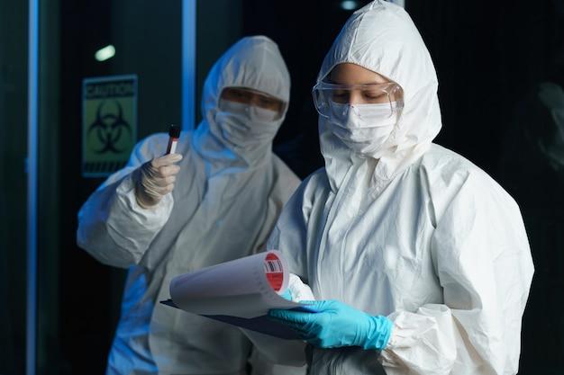 Proces testowania koronawirusa: para naukowców w masce medycznej z okularami ochronnymi w kombinezonie przeciwgazowym, trzymając w ręku probówkę z próbką krwi z informacją o badaniu krwi.
