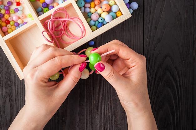 Proces tworzenia biżuterii i koralików. kolorowe koraliki. biżuteria z koralików