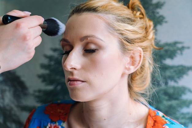 Proces tworzenia makijażu. wizażystka nakładana pędzlem na twarz modelki. portret młoda imbirowa kobieta w piękno salonie. ręka mistrza makijażu z pędzlem tworzy idealną skórę i kolorowy cień do powiek