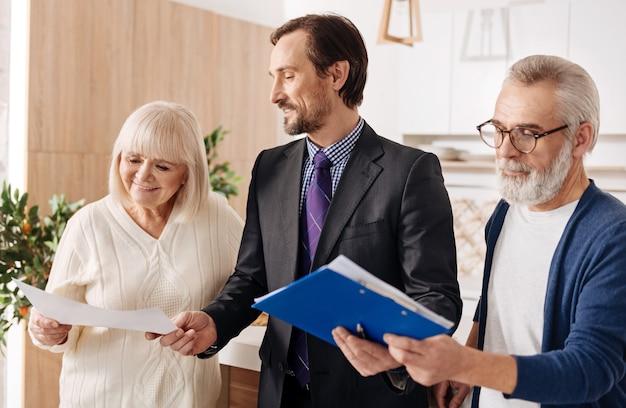 Proces udostępniania informacji prawnych. pewny siebie, pozytywny, konserwatywny prawnik pracujący i prezentujący kontrakt starszej parze klientów, wyrażający jednocześnie pozytywne nastawienie
