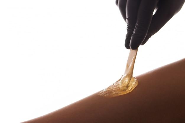 Proces usuwania włosów na kobiecej nodze z depilacją