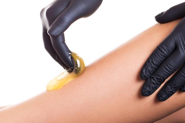 Proces usuwania włosów na nodze kobiety z depilacją