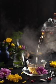 Proces warzenia teadark mood para z gorącej herbaty wylewa się z czajnika kwiaty gorące jedzenie i koncepcja zdrowego posiłku wysokiej jakości zdjęcie