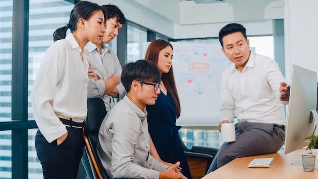 Proces współpracy wielokulturowych biznesmenów wykorzystujących prezentację komputerową i komunikację, spotykający burzę mózgów pomysłów na temat planu pracy współpracowników projektu w nowoczesnym biurze.