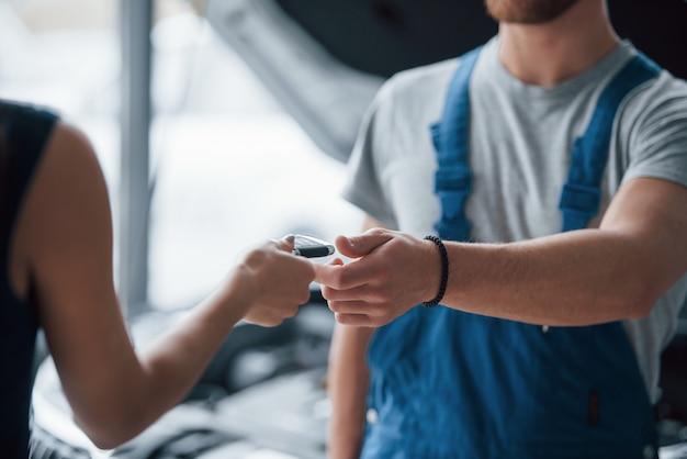 Proces wydawania kluczy. kobieta w salonie samochodowym z pracownikiem w niebieskim mundurze, odbierając jej naprawiony samochód
