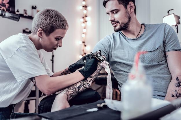 Proces zdrowienia. skoncentrowany, niezwykły mistrz koloryzujący poprzednie tatuaże wypełniający czarne kontury