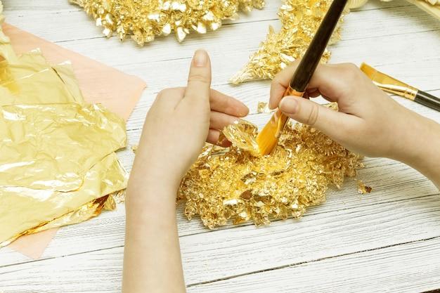 Proces złocenia. kobiece ręce pędzlem. złoty liść