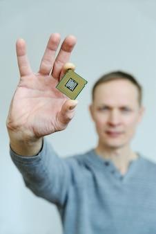 Procesor jest w dłoni mężczyzny. mężczyzna trzyma procesor między dwoma palcami.