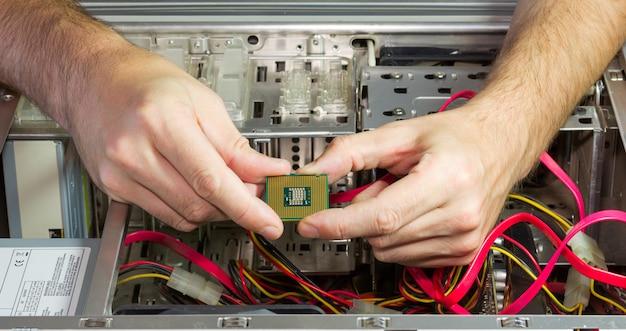 Procesor w rękach ludzi na tle otwartej jednostki systemowej