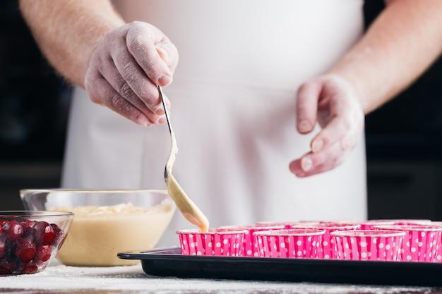 Procesy przygotowania babeczek z bliska na stole. poziomy