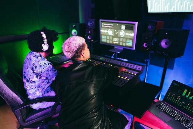 Producenci muzyczni miksujący nowy album w pokoju studia produkcyjnego - skupiają się na kobiecej głowie