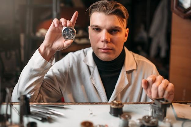 Producent zegarków trzymający w ręku zegarek. narzędzia zegarmistrzowskie na stole