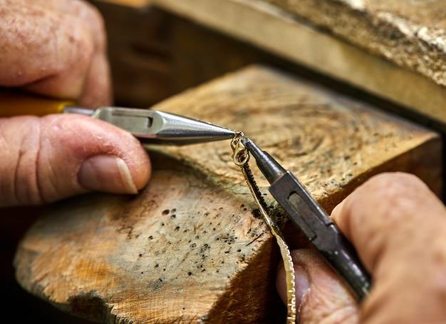 Produkcja ewelry. proces łączenia złotego zamka z bransoletką za pomocą dwóch szczypiec do biżuterii