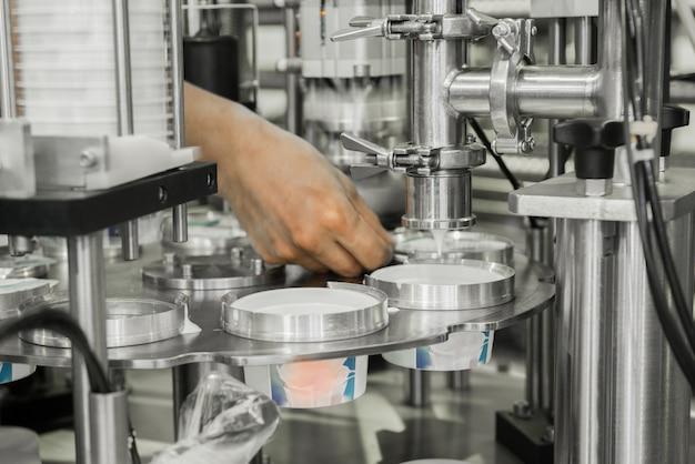 Produkcja i butelkowanie jogurtu w plastikowych kubkach. sprzęt w mleczarni
