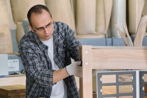 Produkcja mebli, męski stolarz portret w warsztacie drewna co drewniane krzesło.