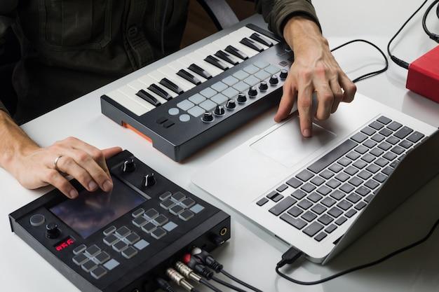 Produkcja muzyki elektronicznej na laptopie za pomocą przenośnej klawiatury midi i elektronicznych procesorów efektów