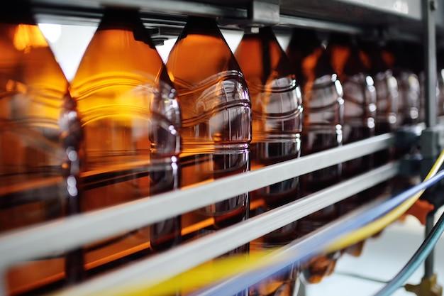 Produkcja przemysłowa butelek plastikowych do napojów niskoalkoholowych, sody i oleju słonecznikowego. puste butelki pet w kolorze brązowym na tle nowoczesnego sprzętu.