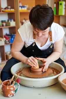 Produkcja rękodzieła mistrz pracuje w glinie za pomocą koła garncarskiego.
