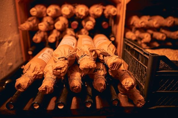 Produkcja winiarni. rzędy butelek wina na półkach w słabo oświetlonej piwnicy