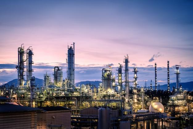 Produkcja zakładu przemysłu naftowego na tle nieba o zmierzchu, rafinerii ropy naftowej i gazu lub zakładu przemysłu petrochemicznego z wieżą destylacyjną