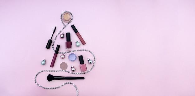 Produkt do makijażu choinka płaska leżała na różowym tle transparentu z miejscem na kopię