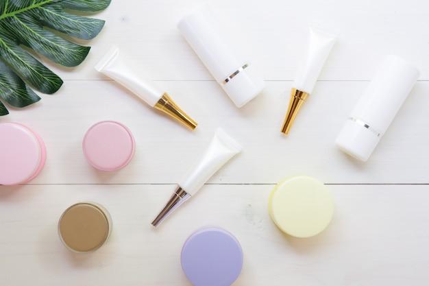 Produkt kosmetyczny i do pielęgnacji skóry i zielonych liści na białym stole drewna