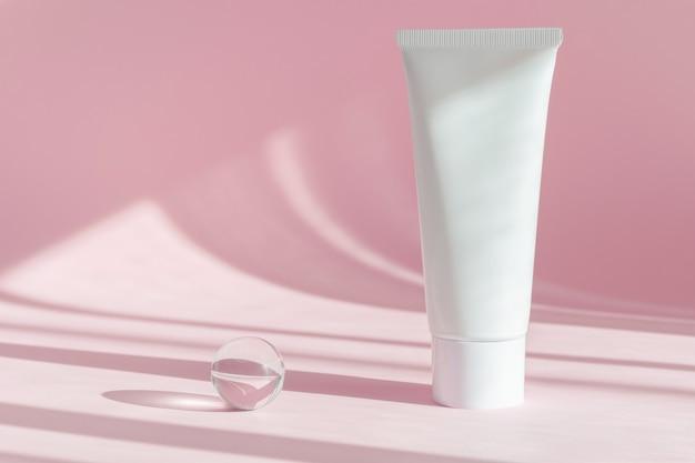 Produkt kosmetyczny . opakowania wellness. brandingowe spa. kosmetyk na różowym tle cienia. krem