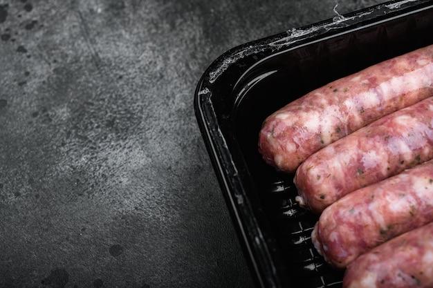 Produkt mięsny do gotowania zapakowany w zestaw pudełek, na czarnym ciemnym tle kamiennego stołu, z miejscem na kopię tekstu
