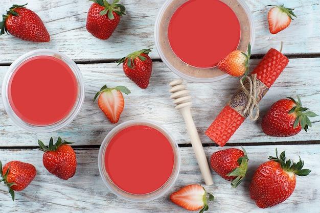 Produkt z twoim tekstem i etykietą ze smakiem lub aromatem truskawek, jagody leżą obok słoików na jasnym drewnianym stole.