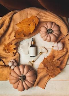 Produkty autumn skin care - butelka kosmetyków, jadeitowy masażer, guasha, jesienne liście, dynie, sweter z dzianiny