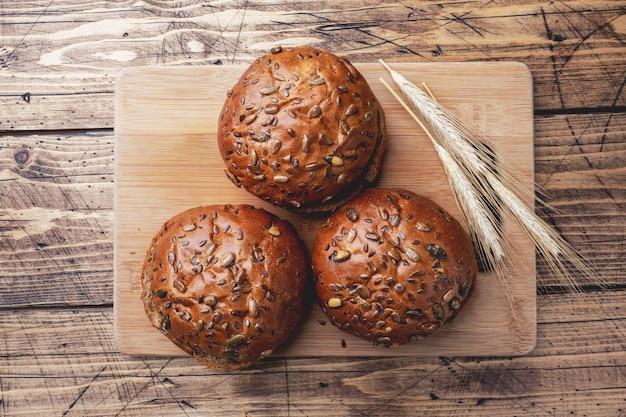 Produkty chlebowe ze zbożami i nasionami na drewnianym stole.