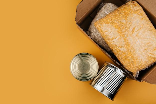 Produkty do darowizny na żółtym tle. warzywa, zboża i konserwy. kopia darowizn żywności.