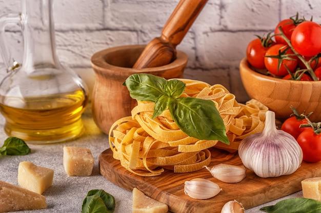 Produkty do gotowania makaronu, pomidorów, czosnku, oliwy, bazylii