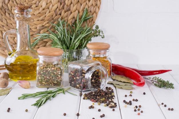 Produkty do gotowania w kuchni, przybory kuchenne, zioła, kolorowe suche przyprawy w szklanych słoikach na białej ścianie