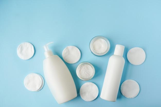Produkty do kąpieli i płatki kosmetyczne na niebieskim tle kopii przestrzeni