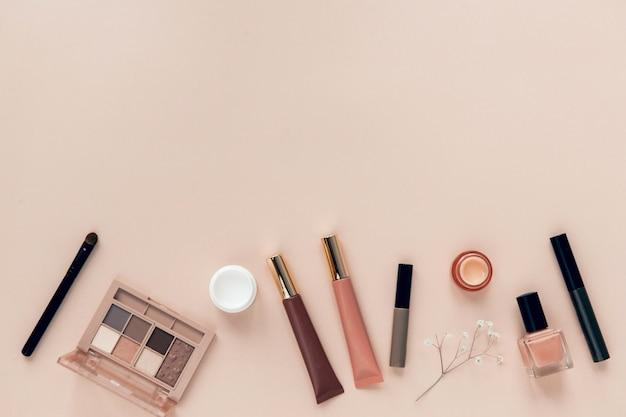 Produkty do makijażu i kosmetyki płasko leżały na beżowym tle