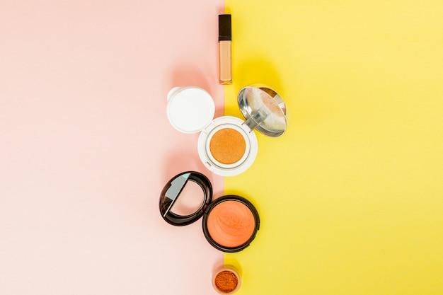 Produkty do makijażu rozlewają się na jasnożółte i różowe tło z miejsca kopiowania
