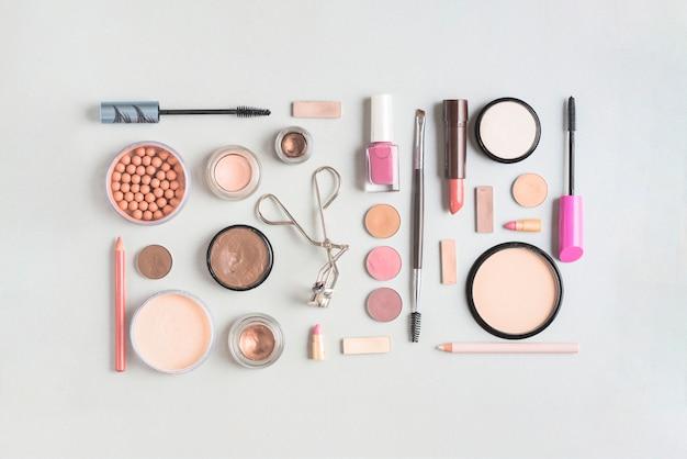 Produkty do makijażu ułożone w prostokątny kształt na białym tle